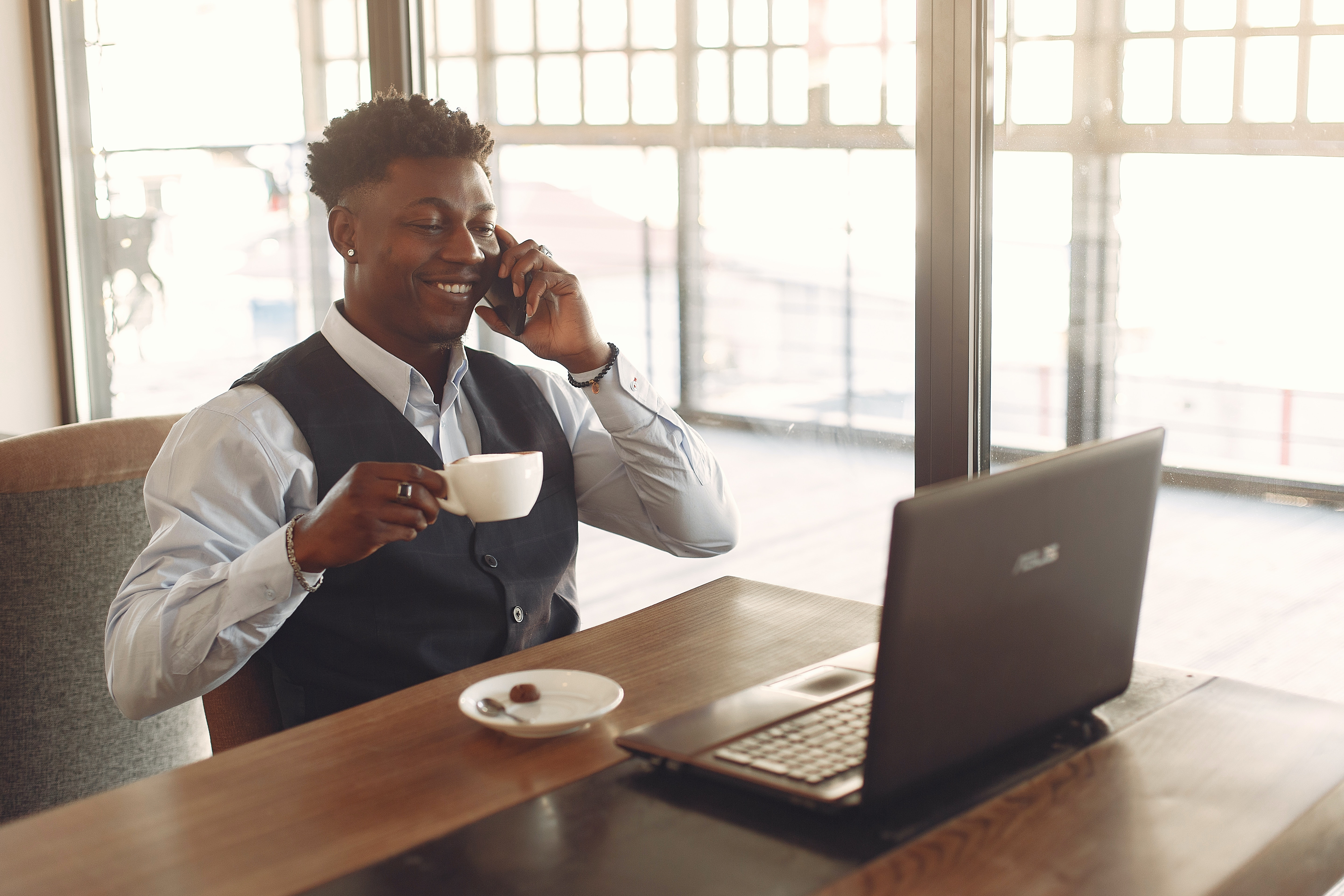 Male professional sitting at a desk drinking coffee